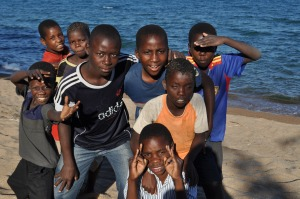 Kids on Lake Malawi playing on the beach with Condom Footballs