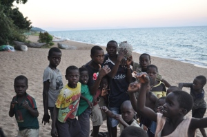 Kids in Malawi playing on the beach with the Condom Footballs